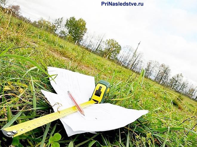 Листы бумаги, рулетка лежат на поле