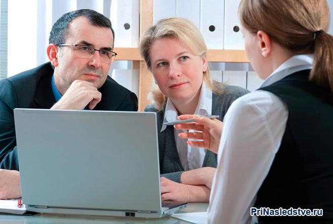 Семейная пара разговаривает с девушкой в офисе