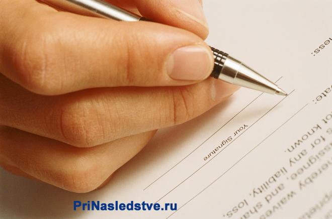 Человек пишет ручкой заявление на листке