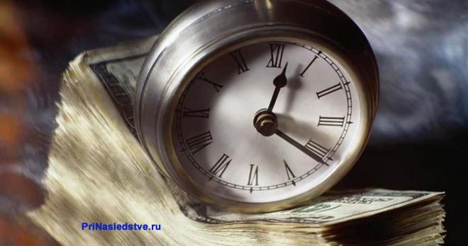 Часы со стрелками стоят на пачке денег