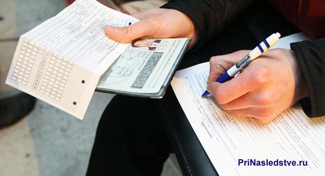 Мужчина держит в руке документы и заполняет бланк