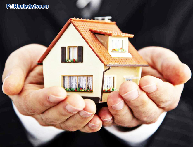 Бизнесмен держит в руках макет дома