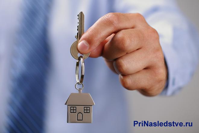 Мужчимна держит ключи от дома в руке