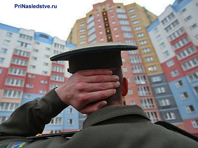 Военный сморит на многоэтажные дома