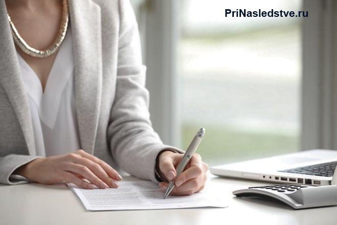 Женщина сидит за столом и заполняет бумаги