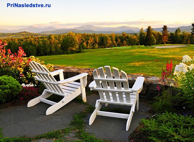 Два дачных кресла стоят в красивом саду