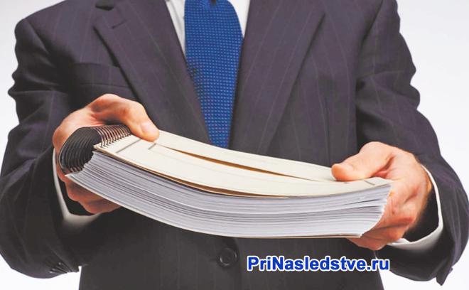 Мужчина в синим галстуке держит в руках папки с документами