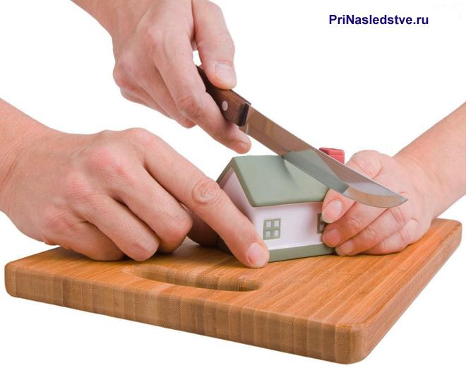 Белый домик с салатовой крышей разрезают на разделочной доске ножом