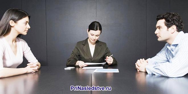 Мужчина и женщина сидят за столом переговоров, сидит женщина на заднем фоне