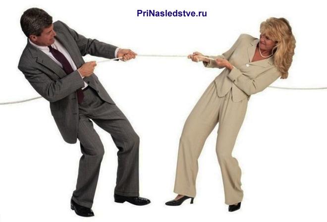Мужчина и женщина в костюмах тянут между собой веревку
