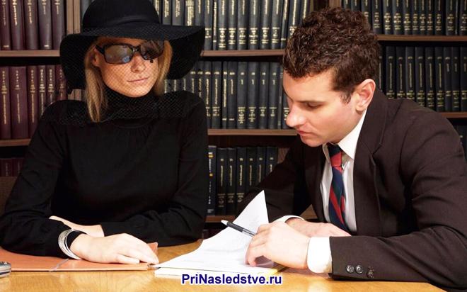 Девушка в черной шляпе и очках подписывает бумаги, рядом сидит мужчина в костюме