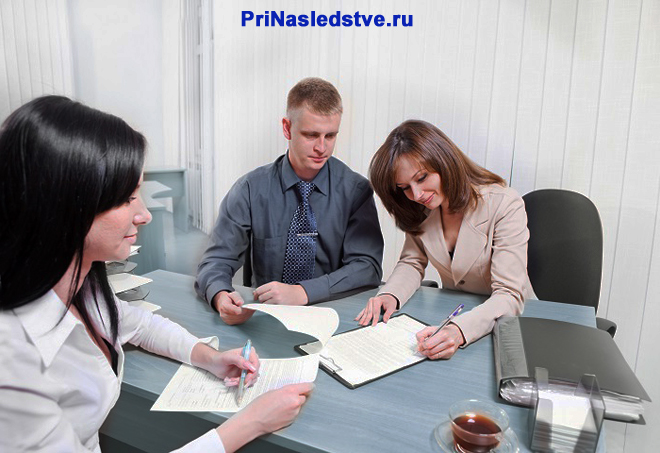 Молодая пара заключает контракт в офисе