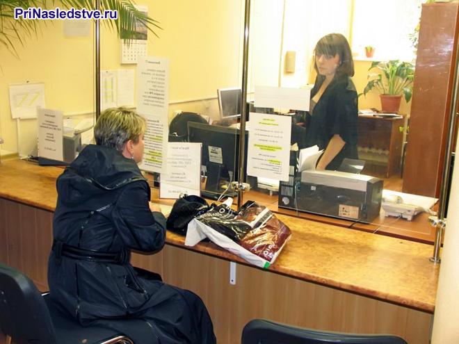 Женщина в плаще подает документы в окно приема граждан