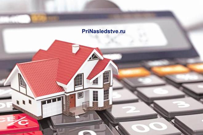 Частный дом с красной крышей стоит на клавишах калькулятора