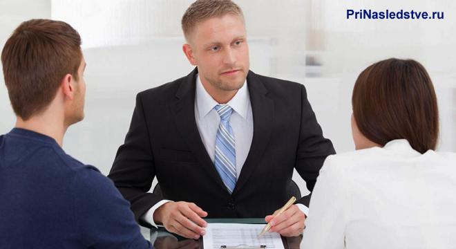 Семейная пара разговаривает с мужчиной в деловом костюме