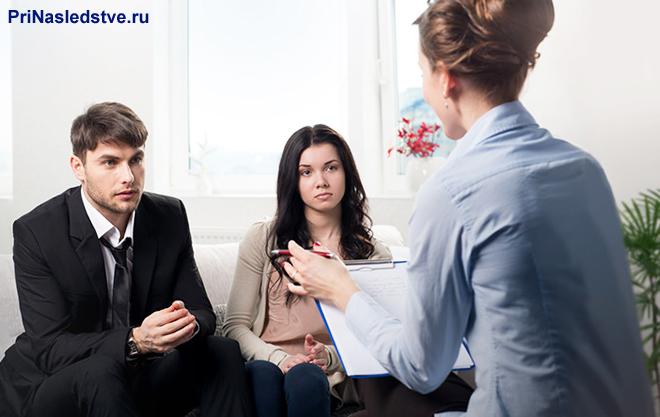 Молодая семейная пара сидит на диване и разговаривает с женщиной
