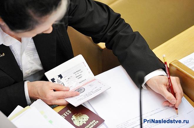 Женщина вписывает свои паспортные данные в бланк