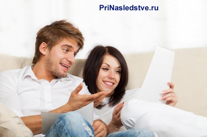 Семейная пара лежит на диване и читает документы