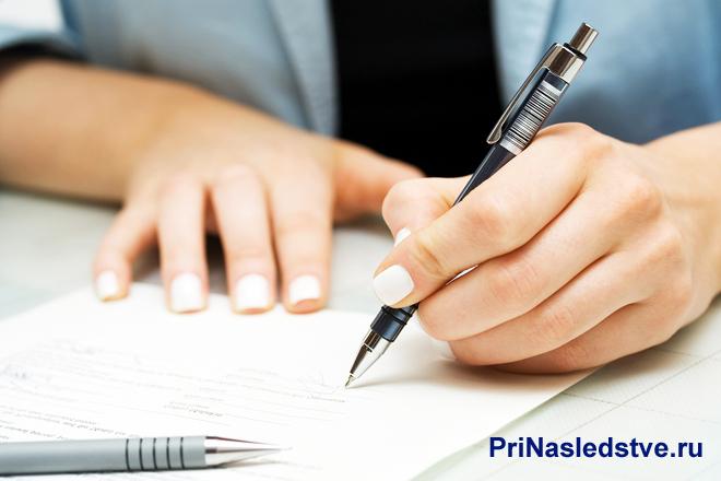 Девушка пишет ручкой на листке
