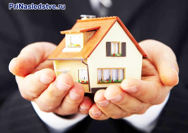 Мужчина держит в руках домик с оранжевой крышей