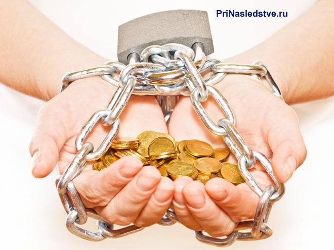 Руки в цепях держат золотые монеты