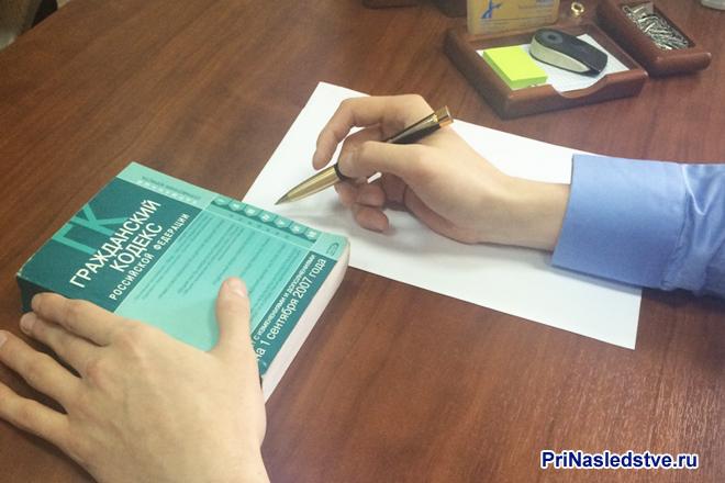 Мужчина сидит за столом, делает записи на листке, рядом лежит Гражданский кодекс РФ