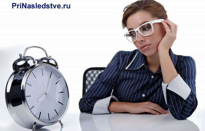 Девушка в очках смотрит на будильник