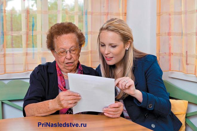 Пожилая женщина и девушка читают документы