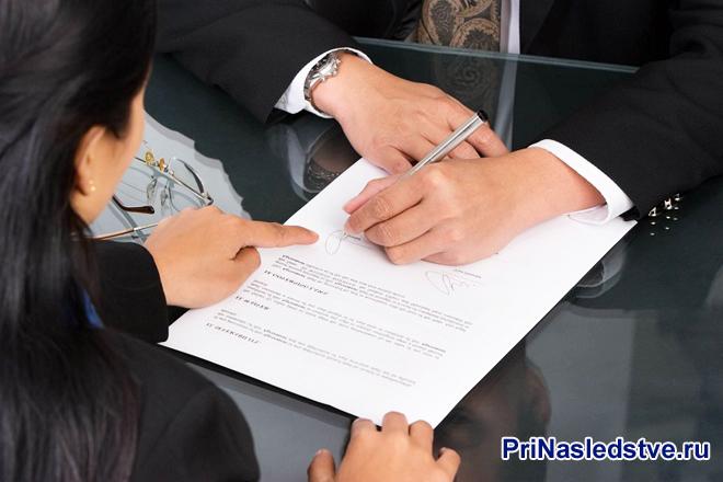 Девушка указывает на пункты в документе мужчине
