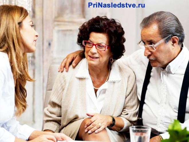 Молодая девушка разговаривает с семейной парой в возрасте