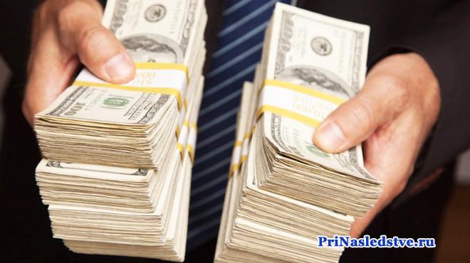 Мужчина в полосатом галстуке держит в руках две пачки денег