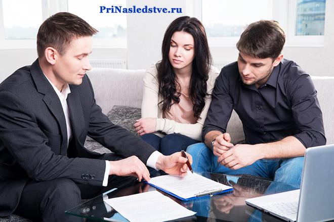 Мужчина в деловом костюме разговаривает и разбирается в документах с молодой парой