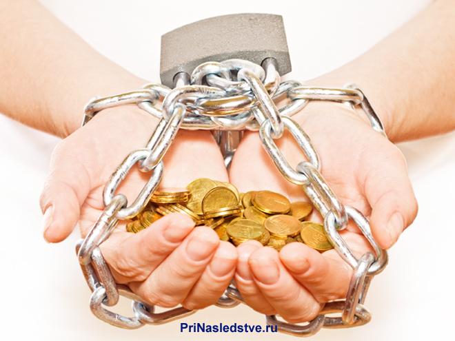 Человеческие руки в наручниках держат золотые монеты