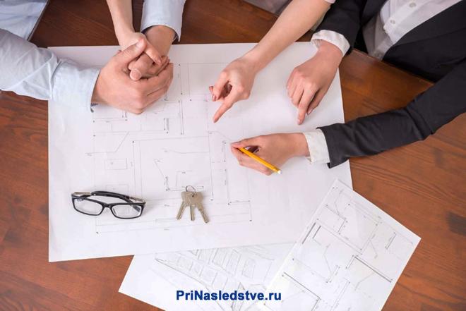 Бизнесмены разложили на столе планы дома