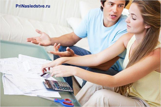 Парень и девушка сидят на диване и считают на калькуляторе
