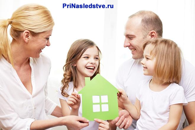 Счастливая семья и зеленый бумажный домик