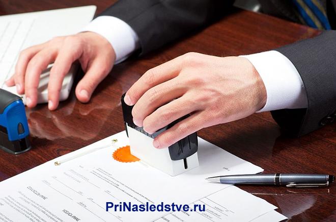 Бизнесмен ставит печать на документах за своим рабочим местом