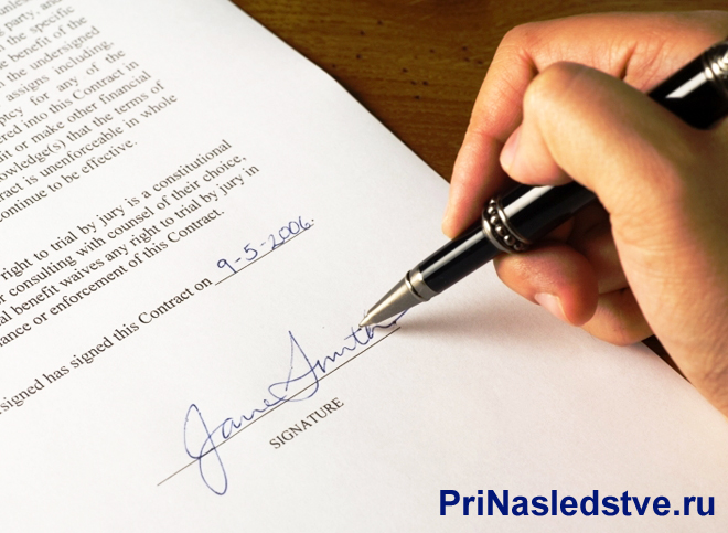 Человек ставит свою подпись в документе