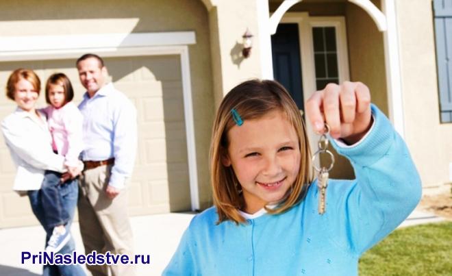 Девочка в голубой кофточке держит ключи, на заднем фоне стоит ее семья