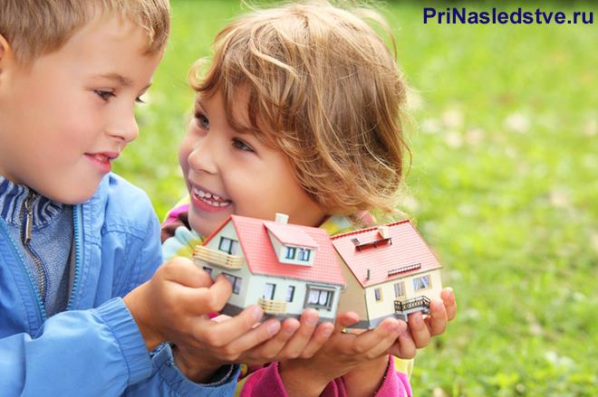 Девочка и мальчик держат в руках игрушечные домики