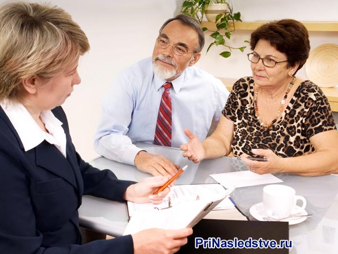 Женщина в костюме общается с семейной парой за столом