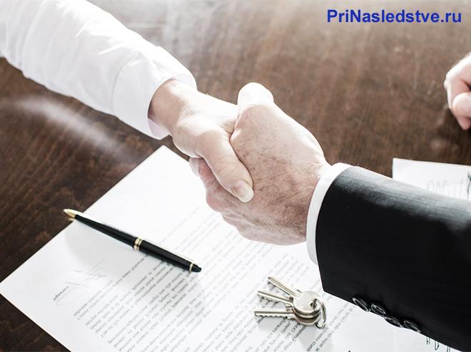 Рукопожатие бизнес-партнеров, на столе лежит контракт