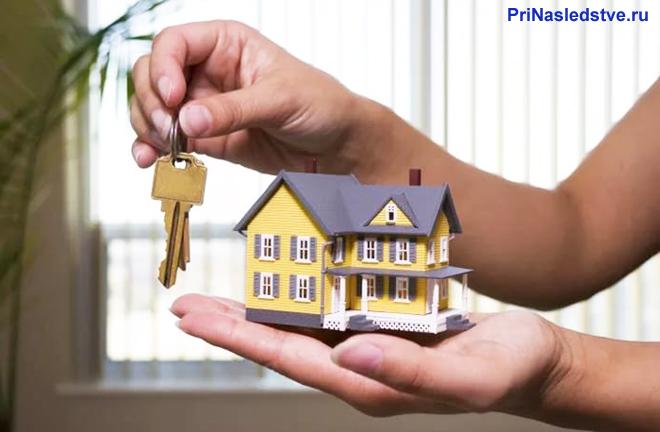 Человек держит в руке желтый домик и ключи