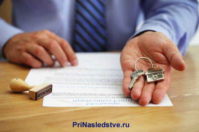 Мужчина с полосатым галстуком держит в руке ключи от квартиры, рядом лежит контракт