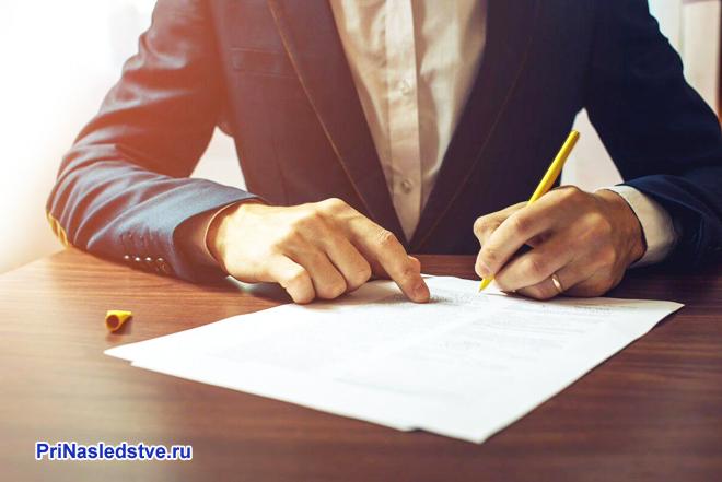 Мужчина в синем костюме сидит за столом и пишет ручкой на листке