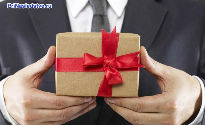 Бизнесмен держит в руках маленький подарочек