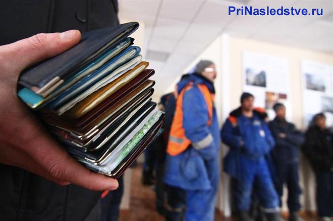 Мужчина держит в руке паспорта, на заднем фоне стоят рабочие