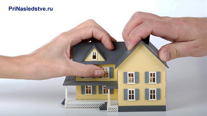 Желтый домик с серой крышей держат человеческие руки