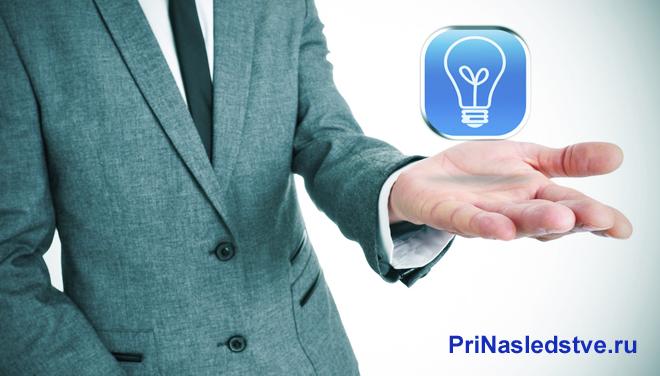 Бизнесмен держит в руке лампочку