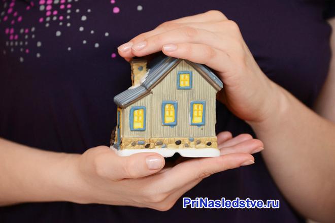 Девушка держит в руках игрушечный домик